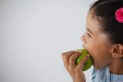 吃苹果的女小学生反对白色背景 免版税库存图片