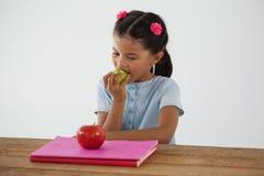 吃苹果的女小学生反对白色背景 库存图片