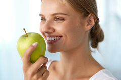 吃苹果的妇女 有白色牙的美丽的女孩咬住苹果计算机的 免版税库存图片
