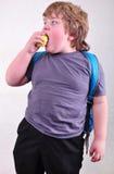 吃苹果的学童画象 免版税库存图片