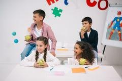 吃苹果的孩子,当坐在教室在断裂期间时 免版税库存照片