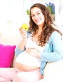 吃苹果的怀孕的愉快的妇女 免版税库存照片