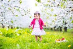 吃苹果的愉快的小孩女孩在开花的庭院里 免版税库存照片