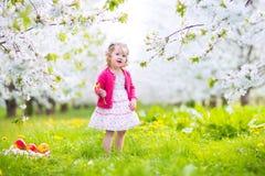 吃苹果的浪漫小孩女孩在开花的庭院里 免版税库存照片