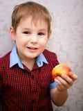 吃苹果的滑稽的孩子 小英俊的男孩用绿色苹果 背景玉米片食物健康宏观工作室白色 果子 享受膳食 免版税库存图片