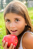 吃苹果的美丽的九岁的女孩 图库摄影
