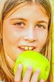 吃苹果的美丽的九岁的女孩 库存照片