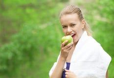 吃苹果的运动员妇女 免版税库存照片