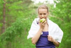 吃苹果的运动员妇女 库存照片