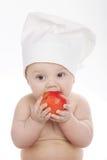 吃苹果的逗人喜爱的矮小的厨师 免版税库存照片