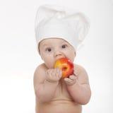 吃苹果的逗人喜爱的矮小的厨师 免版税库存图片