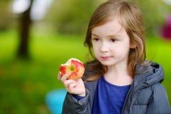 吃苹果的逗人喜爱的矮小的学龄前儿童女孩 库存图片