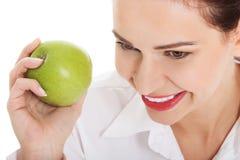吃苹果的年轻女商人。 库存照片