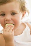 吃苹果的婴孩户内 免版税图库摄影