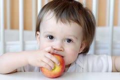 吃苹果的婴孩 免版税库存图片