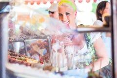 吃苹果糖的妇女在慕尼黑啤酒节或Dult 免版税库存图片