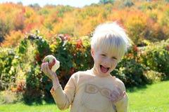 吃苹果计算机的愉快的笑的孩子在果树园 免版税库存图片