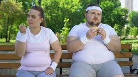 吃苹果,肥胖人的肥胖女孩食用汉堡,适当的食物单独选择  股票视频