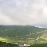 吃草与公羊和绵羊在山在路在乔治亚有薄雾的天空背景的 库存图片