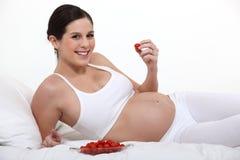 吃草莓的一名孕妇 库存图片