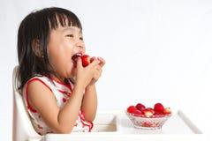 吃草莓的亚裔中国小女孩 免版税库存图片