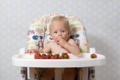 吃草莓的女婴 免版税库存照片