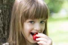 吃草莓的小美丽的女孩 免版税库存照片