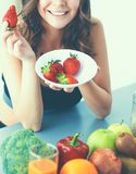 吃草莓的微笑的妇女 女性面孔画象的关闭 免版税图库摄影