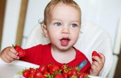 吃草莓的愉快的小孩男孩 免版税库存照片