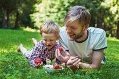 年轻吃草莓的父亲和他的儿子在公园 野餐 室外纵向 免版税库存图片
