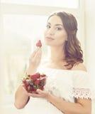 吃草莓的美丽和女孩 图库摄影