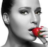 吃草莓的美丽的少妇 免版税库存照片