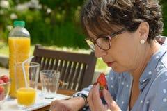 吃草莓的美丽的成熟妇女,外面 免版税库存图片
