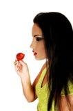 吃草莓的青少年的女孩。 免版税库存图片