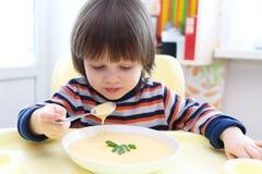 2年吃菜奶油色汤的男孩 健康营养 免版税图库摄影