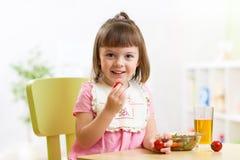 吃菜沙拉的儿童女孩在家 免版税库存照片