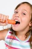 吃菜的逗人喜爱的快乐的女孩 免版税库存图片