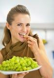 吃葡萄的愉快的少妇 库存照片