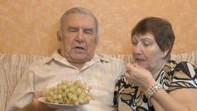 吃葡萄莓果的年长夫妇 他们互相喂养 愉快的时间 股票录像