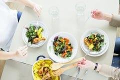 吃蔬菜沙拉与的两个少妇顶视图chiken和土豆 免版税库存照片