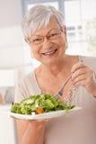 吃蔬菜沙拉的愉快的老妇人 库存图片