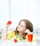 吃蕃茄新鲜的沙拉空的空间背景的儿童女孩 免版税库存照片