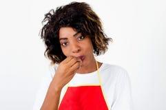 吃蕃茄的一位年轻厨师的画象 免版税库存照片