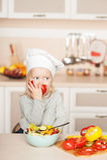 吃蕃茄的小女孩,当烹调沙拉时 免版税库存照片
