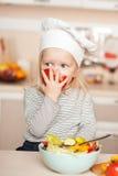 吃蕃茄的逗人喜爱的女孩,当烹调沙拉时 免版税库存照片