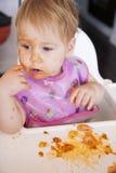 吃蕃茄膳食用她的手的婴孩 图库摄影