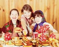 吃薄煎饼用鱼子酱的妇女在Shrovetide期间 免版税库存照片