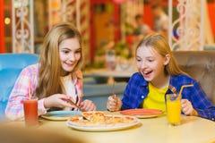 吃薄饼和喝汁液的两个微笑的女孩室内 免版税图库摄影