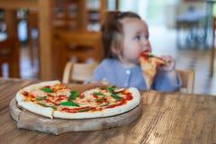 吃薄饼的女婴在意大利餐馆,健康,不健康的食物,儿童` s快餐 免版税图库摄影