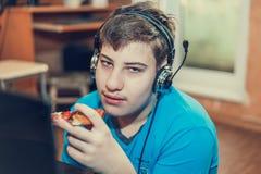 吃薄饼的少年坐在膝上型计算机 图库摄影